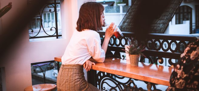 Woman at a bar drinking through a straw