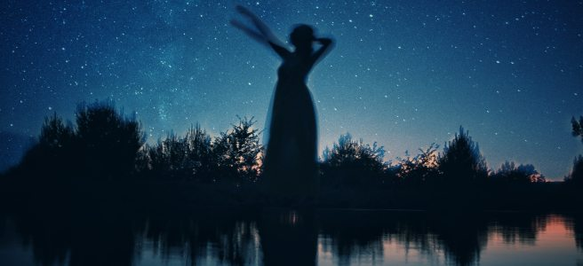 blurry woman at night with stars behind her